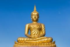 Große goldene Buddha-Statue, die auf Hintergrund des blauen Himmels sitzt Lizenzfreies Stockbild
