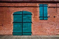 Große grüne Metalltüren im alten Ziegelsteingebäude stockfotografie