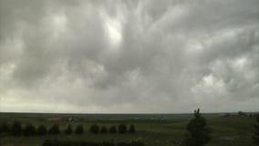 Große graue Sturmwolken über beträchtlichem grünem Land stock footage