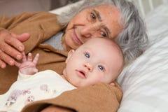 Große Großmutter, die mit Baby niederlegt Lizenzfreie Stockbilder
