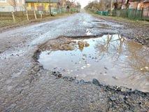 Große Grube füllte mit Wasser in der Asphaltbedeckung, gebrochene Straße, Reflexion der Umwelt im Wasser, ukrainische Straßen Lizenzfreie Stockfotos