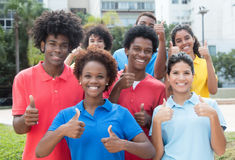 Große Gruppe erfolgreicher Mann und Studentinnen, die Daumen zeigen lizenzfreies stockfoto