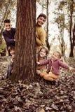 Große Gruppe Kinder Glückliche Kinder, die hinter Baum sich verstecken lizenzfreie stockfotografie