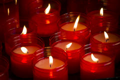 Große Gruppe rote Kerzen, die in der Dunkelheit glänzen Lizenzfreies Stockbild