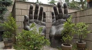 Große Hände der Steinskulptur zum Himmel stockfotos