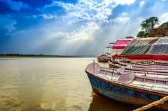Große hölzerne Boote im Wasser mit bewölktem Himmel und Sonnenstrahlen Stockfoto