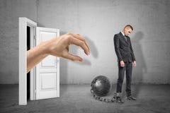 Große Hand, die durch weißen Eingang erreicht, um jungen traurigen Geschäftsmann zu fangen, der an Metallball auf grauer Wand ang lizenzfreies stockbild