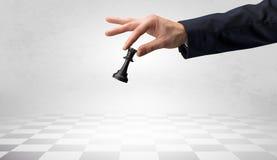 Große Hand, die seinen nächsten Schritt auf Schachspiel unternimmt Stockfotos