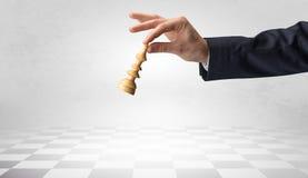 Große Hand, die seinen nächsten Schritt auf Schachspiel unternimmt Lizenzfreies Stockfoto