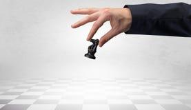 Große Hand, die seinen nächsten Schritt auf Schachspiel unternimmt Lizenzfreie Stockfotografie