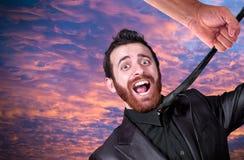 Große Hand, welche die Krawatte des jungen Geschäftsmannes ergreift Lizenzfreie Stockbilder