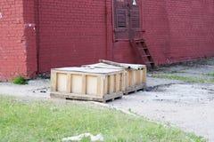 Große Holzkisten mit Waren stehen draußen im Freien im Lager eines Industrieunternehmens gegen eine Wand des roten Backsteins lizenzfreies stockbild