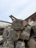 Große konkrete Klumpen mit verdrehtem Metall und Industriegebäude Lizenzfreies Stockfoto