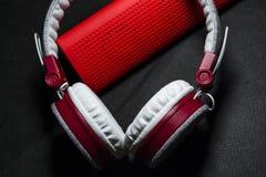 Große Kopfhörer von weißen und roten Farben Klein die tragbaren Sprecher Schwarzer Hintergrund Moderne bewegliche Elektronik gerä stockfotos
