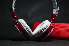 Große Kopfhörer von weißen und roten Farben Klein die tragbaren Sprecher Schwarzer Hintergrund Moderne bewegliche Elektronik gerä lizenzfreie stockfotos