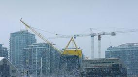 Große Kräne in der Stadt mit dem Schnee-Fallen stock footage