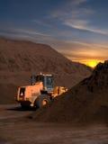 Große Löffelbagger- und Mutterbodenstapel am Sonnenuntergangsonnenaufgang Stockfoto