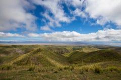 Große Landschaftsansichtwolken, -berge und -gras lizenzfreie stockfotos