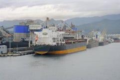 Große Lieferungsfrachter in einem besetzten Porthafen Stockbilder