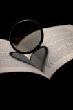 Große Linse, die auf einem bw des offenen Buches steht Lizenzfreie Stockbilder