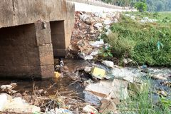Große Mülldeponie durch die Straße und den Fluss stockfoto