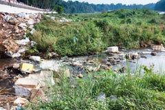 Große Mülldeponie durch die Straße und den Fluss Lizenzfreies Stockbild