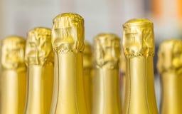Große Menge goldene Sektflaschehälse und Spitzenkappen auf dem Stand den hellen Hintergrund Stockfoto