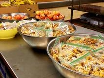 Große Mengen der Mischimbisse, Äpfel in den Schüsseln Pappschachtel Bananen stockfotos