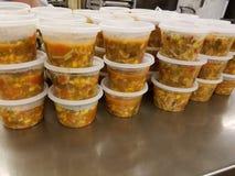Große Mengen gekochtes Essen in den Plastikbehältern auf Metalltabelle in der industriellen Küche stockfotografie