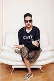 Große Mutterfrau des recht stilvollen Afroamerikaners gut gekleidet Swag entspannen sich zu Hause, Leoparddruck auf clothers Art  Stockbild