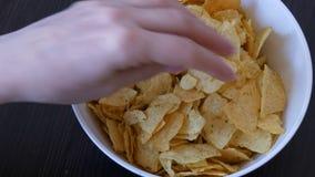 Große Platte mit Kartoffelchips auf dem Tisch Weibliche Hände mit schönen Manikürenehmenchips stock footage
