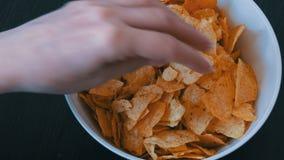 Große Platte mit Kartoffelchips auf dem Tisch Weibliche Hände mit schönen Manikürenehmenchips stock video