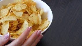 Große Platte mit Kartoffelchips auf dem Tisch Weibliche Hände mit schönen Manikürenehmenchips stock video footage
