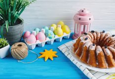 Große Platte mit Kuchen und handgemalten bunten Eiern, auf Tuch auf blauem Hintergrund Abschluss oben Dekoration für Ostern, lizenzfreie stockbilder