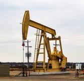 Große Pumpe Jack des Gelb-912 auf Öl oder Gassonde mit umgebender Ausrüstung gegen einen bewölkten Himmel stockbild
