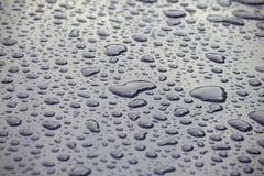 Große Regentropfen auf einer glatten schwarzen Oberfläche Beschaffenheit Nahaufnahme stockbilder