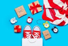 Große rote Gummiüberschuhe in der kühlen Einkaufstasche, Wecker und gestreift Lizenzfreie Stockbilder