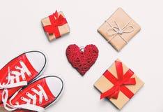 Große rote Gummiüberschuhe, Herz formten Spielzeug und schöne Geschenke Lizenzfreie Stockfotos