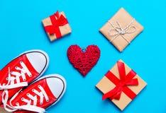 Große rote Gummiüberschuhe, Herz formten Spielzeug und schöne Geschenke auf dem wo Lizenzfreie Stockfotos
