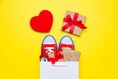 Große rote Gummiüberschuhe, schöne Geschenke und Wecker im kühlen shoppi Lizenzfreie Stockbilder