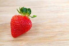 Große rote reife Erdbeere auf Holztisch Lizenzfreies Stockbild