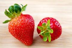 Große rote reife Erdbeere auf Holztisch Stockfotos