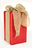 Große rote Weihnachtsgeschenkbox eingewickelt im Leinwand-Bogen Stockfoto