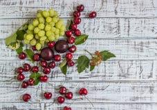 Große süße saftige Kirschen, Pflaumen und Trauben, Laub und Blumen auf einem hölzernen Hintergrund stockfoto