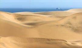Große Sanddünen Ozean mit Schiffen und Boot im Hintergrund Lizenzfreie Stockfotos