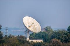 Große Satellitenschüssel auf dem Wald über bewölktem Hintergrund lizenzfreie stockfotografie