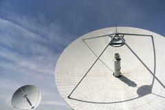 Große Satellitenschüssel gegen leicht bewölktes Blau s Stockfotografie
