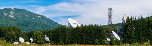 Große Satellitenschüsselantennen versteckt in grüner Kieferwaldsatellitenkommunikations-center in Cheia, Prahova, Rumänien lizenzfreies stockbild