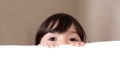 Große schöne Augen, die über weißen Kopien-Raum spähen Stockfotografie