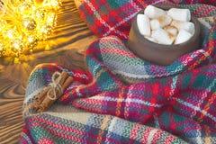 Große Schale heißer Kakao mit Eibisch, Zimt und warmer Decke auf einer alten Weinlese hölzern und Weihnachtslicht Gemütliches Wei Stockfotos